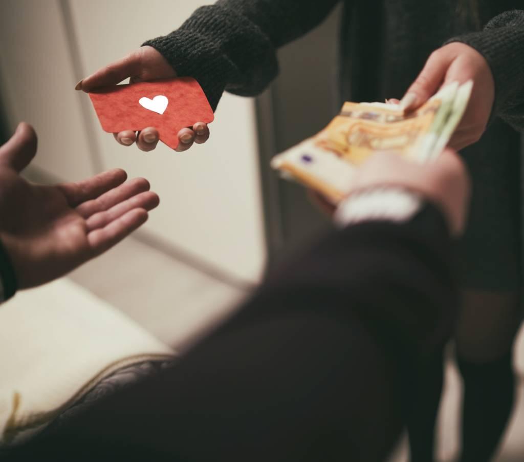 Aseguranza medica barata comprar un seguro medico mujer con sweater intercambiando dinero por una tarjeta de seguro de salud con un corazon rojo