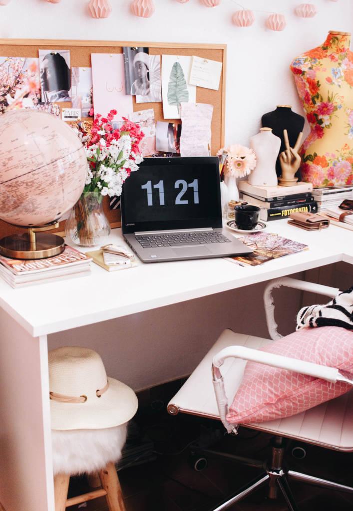 Aseguranza Medica Barata Trabajador Independiente en Fotografia con escritorio y silla blanca con laptop negra, globo de mundo rosa, almohada rosa, flores y decoracion femenina