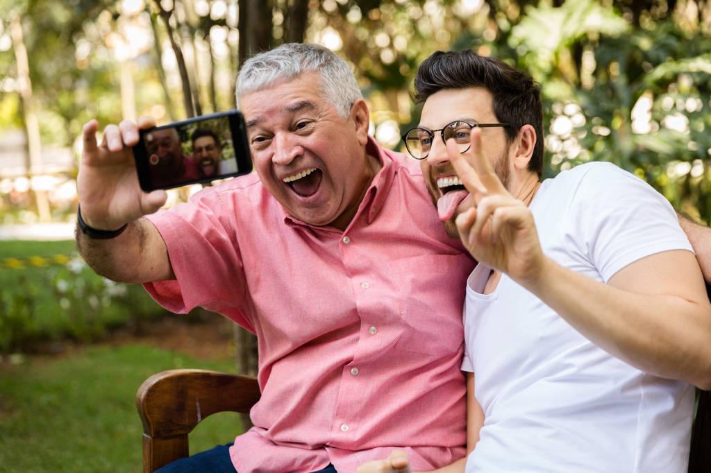 Aseguranza Medica Barata Salud del hombre Día del Padre Padre en una camisa rosa e hijo en un t-shirt blanco tomandose una foto selfie sonriendo y sacando la lengua en el parque