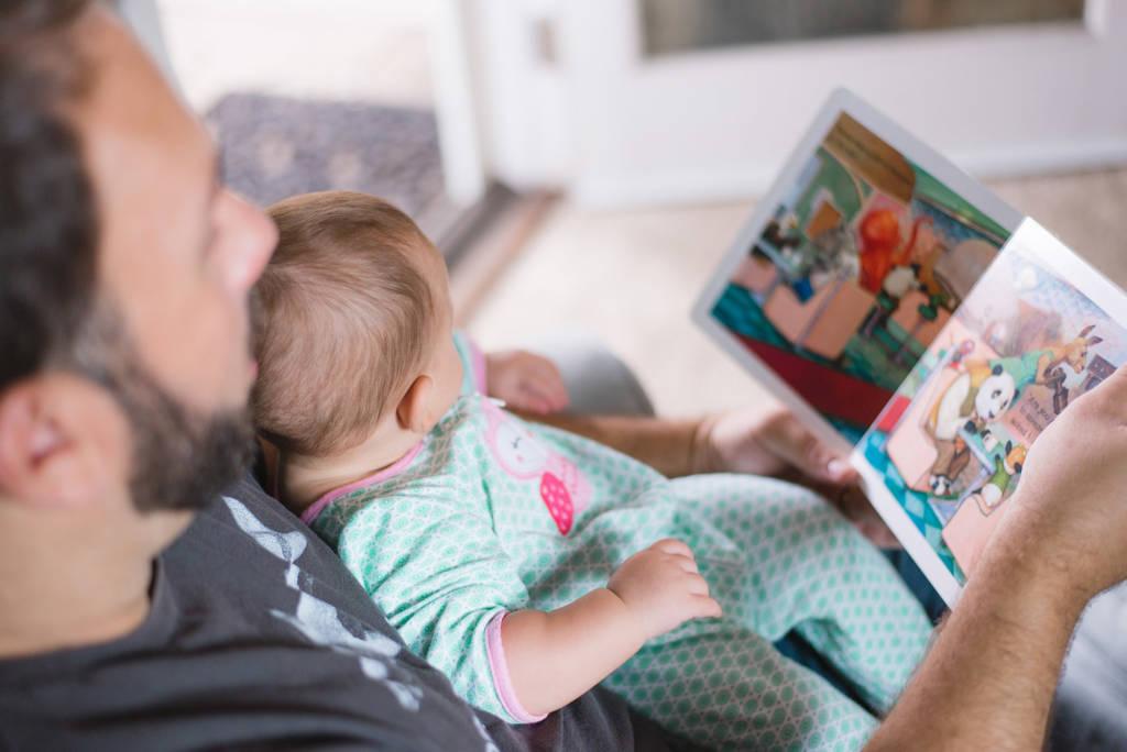 Aseguranza Medica Barata Salud del hombre Día del Padre Padre cargando en un t-shirt gris cargando a hija en oneside azul leyendole una historia para dormir en la casa