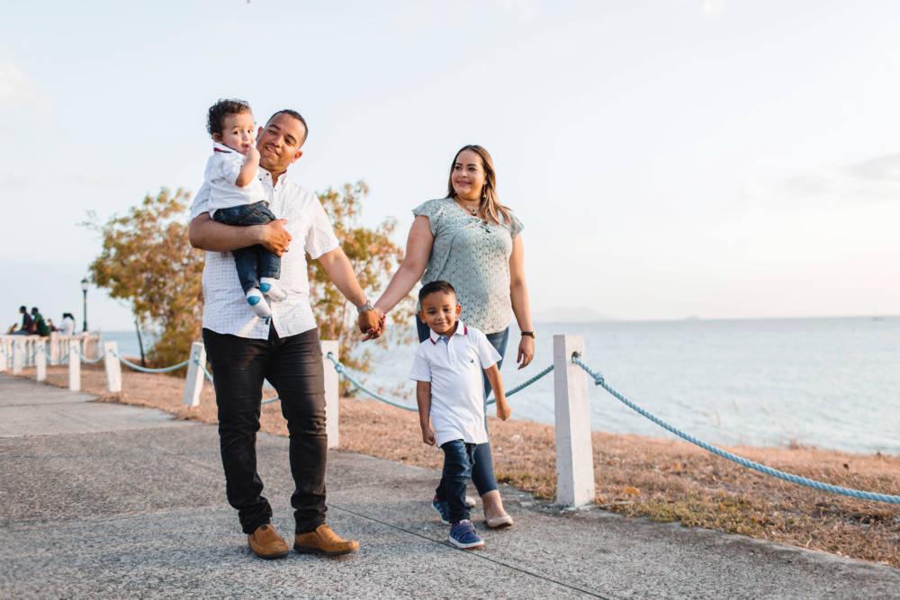 Aseguranza Medica Barata - Seguro Medico en Estados Unidos - Familia Latina caminando en el parque madre y padre agarrados de manos y cargando a hijo